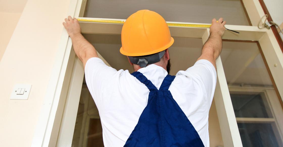 Worker taking measurements for a new door