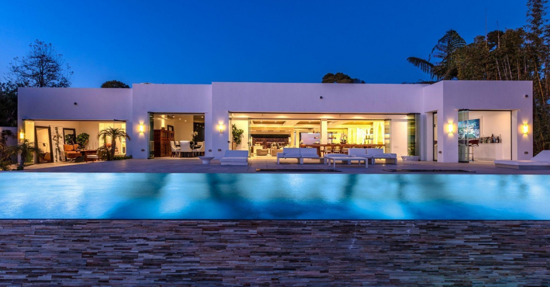House at night with frameless glass doors open