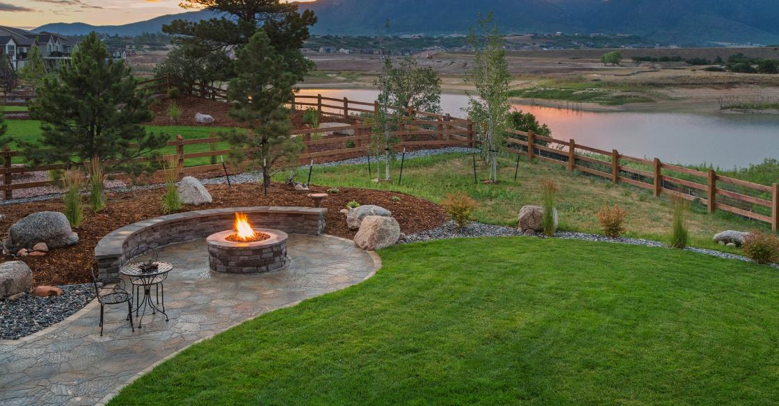 Landscaped backyard with a firepit