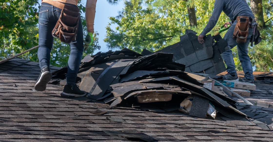 roofers replacing shingles on a roof