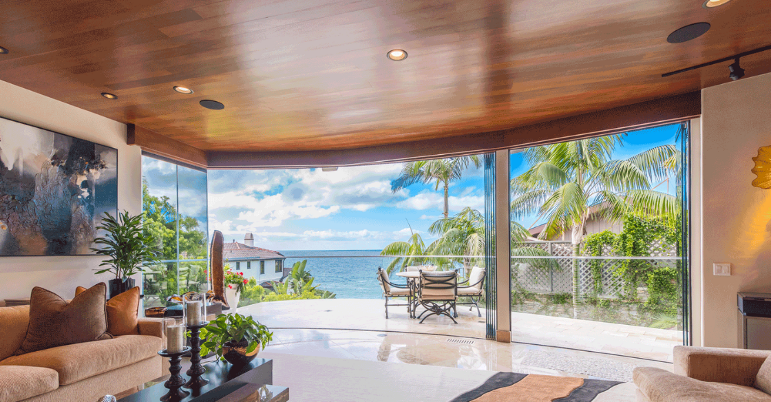House with beautiful views of the ocean seen through a fully open frameless glass door system