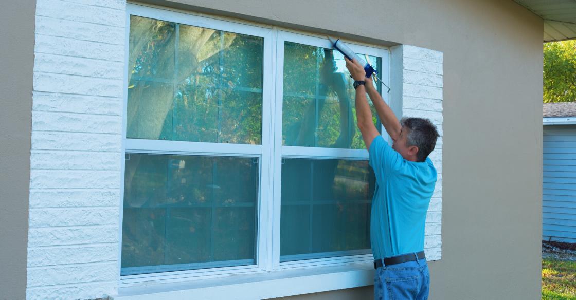 Man weatherproofing windows for winter