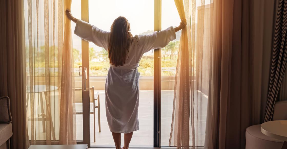 Room standing in front of her hotel room's sliding glass doors
