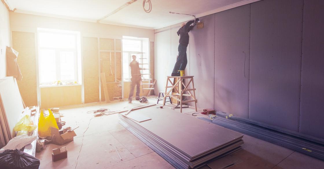 Builders installing drywall